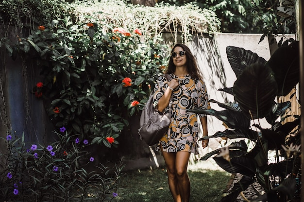 Niña con una mochila, con gafas de sol, en un jardín tropical
