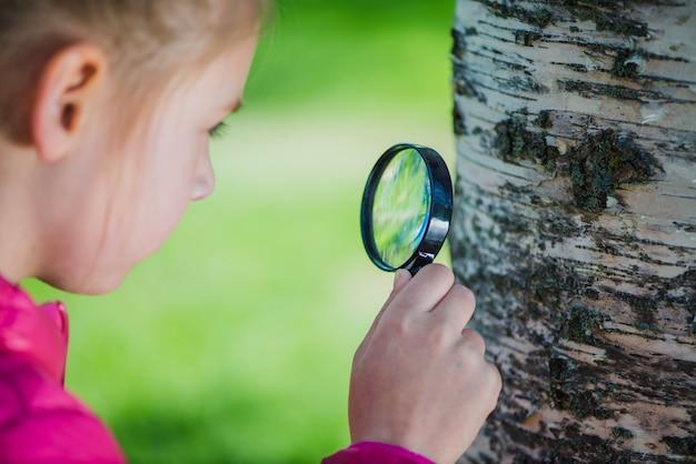 Niña concentrada analizando un tronco