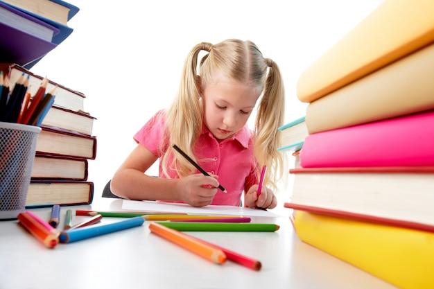 Niña concentrada rodeada de libros de colores