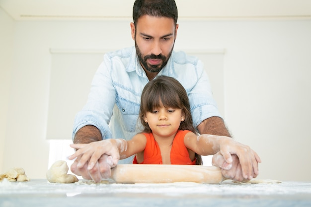 Niña concentrada y su papá amasando y rodando masa sobre la mesa de la cocina con harina desordenada.