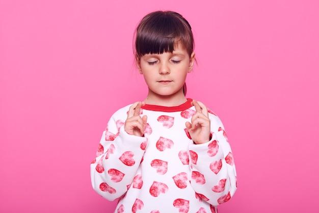 Niña concentrada vistiendo un jersey casual con corazones manteniendo los ojos cerrados y los dedos cruzados, aislado sobre una pared rosa.