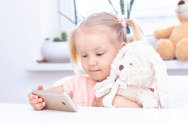 Una niña con un conejito de juguete usando un teléfono móvil, un teléfono inteligente para hacer videollamadas, hablando con familiares, una niña sentada en su casa, una cámara web en línea, haciendo una videollamada.
