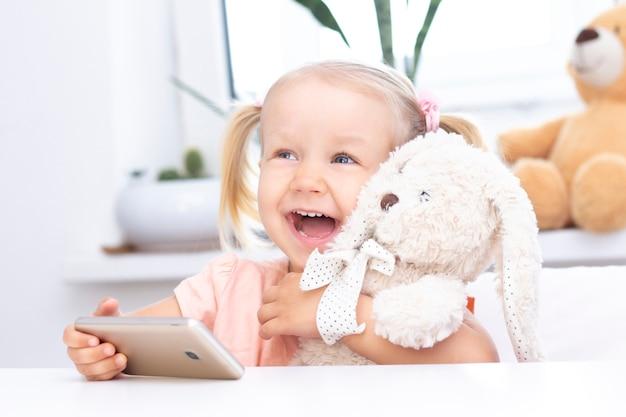 Niña con un conejito de juguete usando un teléfono móvil, un teléfono inteligente para videollamadas, hablando con parientes, una niña sentada en su casa, cámara web en línea, haciendo una video llamada.