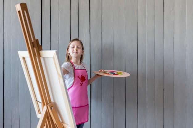 Niña confiada que pinta en el caballete que se opone a la pared de madera gris