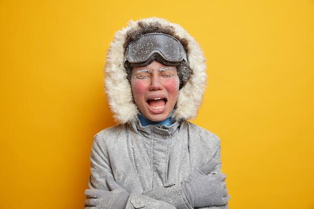 Niña congelada disgustada con ropa de invierno tiembla de frío y se abraza a sí misma expresa emociones negativas tiene la cara roja cubierta de escarcha.