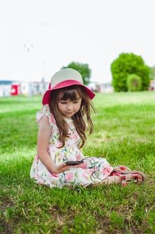 Niña contenta con un teléfono móvil en la mano