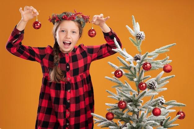 Niña con corona de navidad en camisa a cuadros sosteniendo bolas de navidad mirando a la cámara feliz y sonriente de pie junto a un árbol de navidad sobre fondo naranja