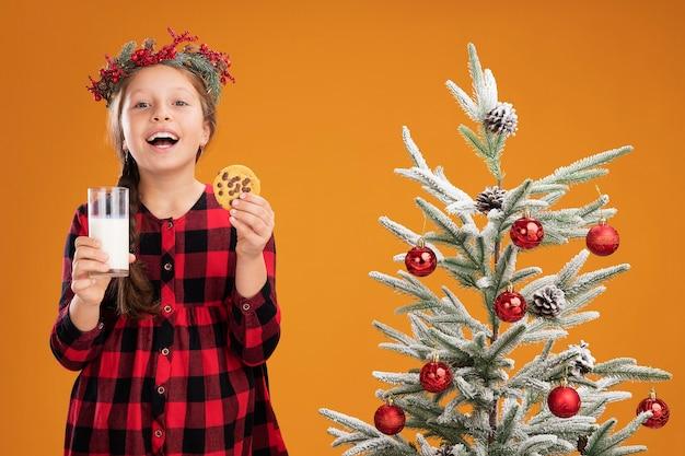 Niña con corona de navidad en camisa a cuadros sosteniendo un vaso de leche y galletas de pie feliz y alegre junto a un árbol de navidad sobre la pared naranja