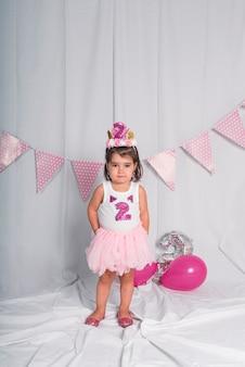 Una niña con una corona y un tutú celebrando su segundo cumpleaños en blanco.