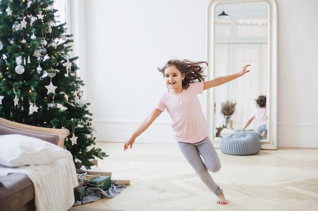 Niña corre alrededor de la habitación decorada, árbol de navidad