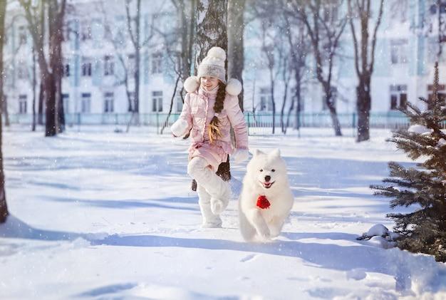 La niña corre con un cachorro samoyedo en un parque cubierto de nieve en nochevieja