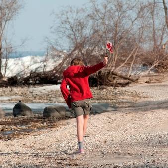Niña corriendo a lo largo de la costa del lago winnipeg en gimli, manitoba canadá