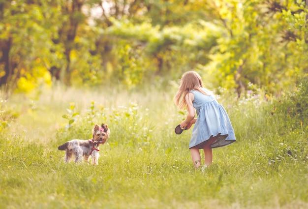 Niña corriendo con el perro en el campo