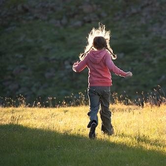 Niña corriendo por un prado iluminado por el sol