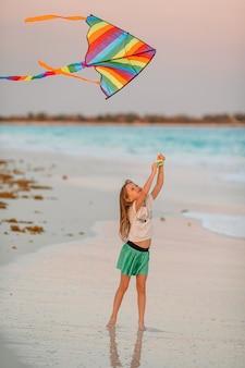 Niña corriendo con volar la cometa en la playa tropical. niño juega en la orilla del océano.
