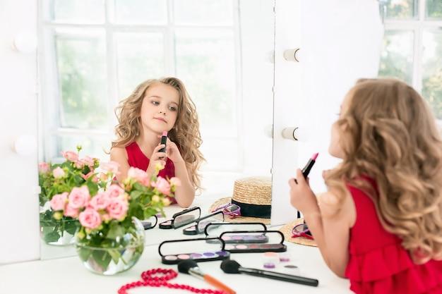 Una niña con cosméticos. ella está en el dormitorio de la madre, sentada cerca del espejo.