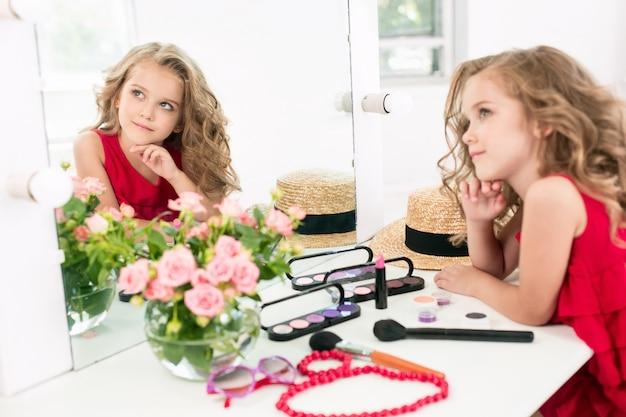 Una niña con cosméticos sentado cerca del espejo.