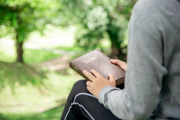 Una niña cristiana asiática con una funda de cuero de la biblia.