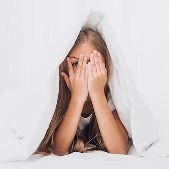 Niña cubriendo sus ojos debajo de la manta