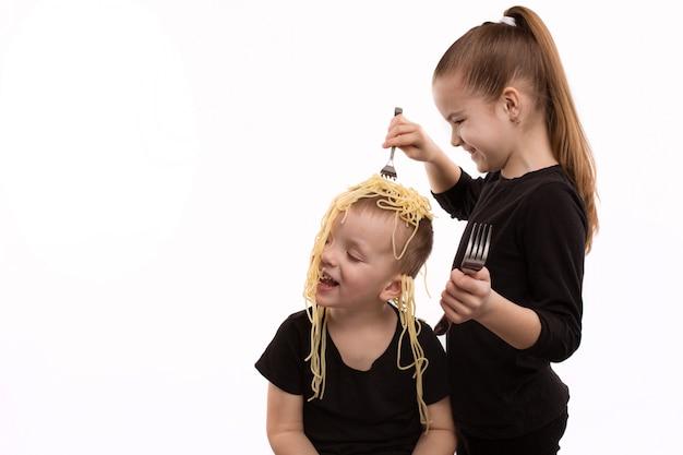 La niña cuelga fideos en las orejas, haciendo trampa. concepto del día de los inocentes.