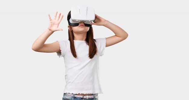 Niña de cuerpo completo emocionada y entretenida, jugando con gafas de realidad virtual