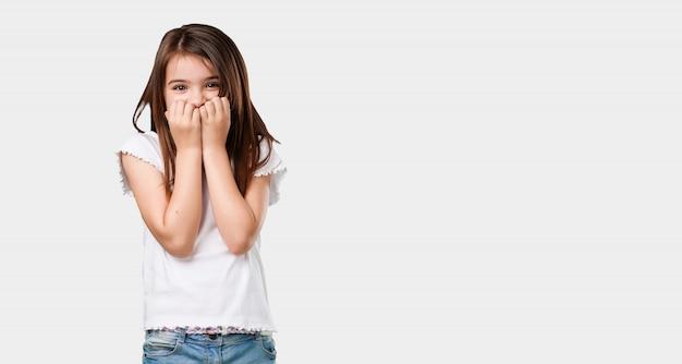 Niña de cuerpo completo mordiéndose las uñas, nerviosa y muy ansiosa y asustada por el futuro.