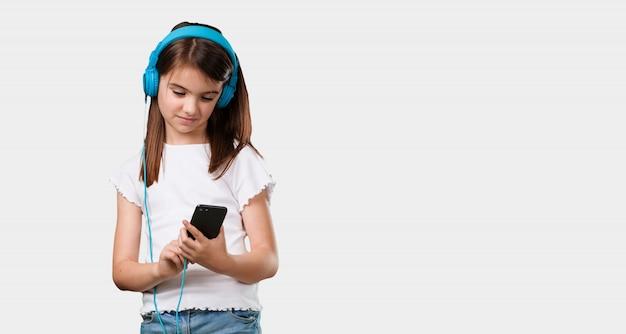 Niña de cuerpo completo relajada y concentrada, escuchando música con su teléfono móvil, sintiendo el ritmo y descubriendo nuevos artistas, con los ojos cerrados.