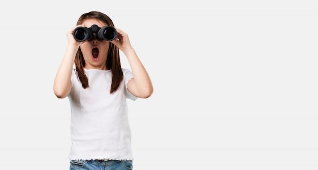 Niña de cuerpo completo sorprendida y asombrada, mirando con binoculares en la distancia algo interesante.
