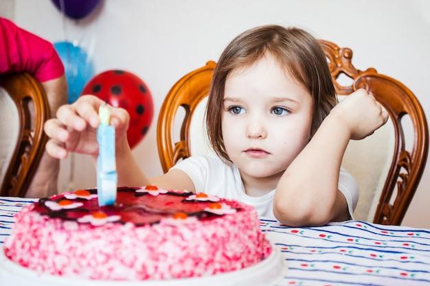 Niña, cumpleañera soplando velas en la tarta, celebración de cumpleaños con amigos