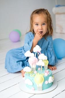 Niña de cumpleaños feliz de tener un pastel de cumpleaños