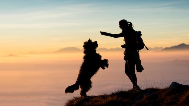 Niña da comida a su perro en las montañas