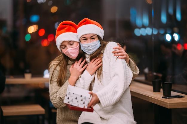 La niña le da un regalo a su amiga en caffe