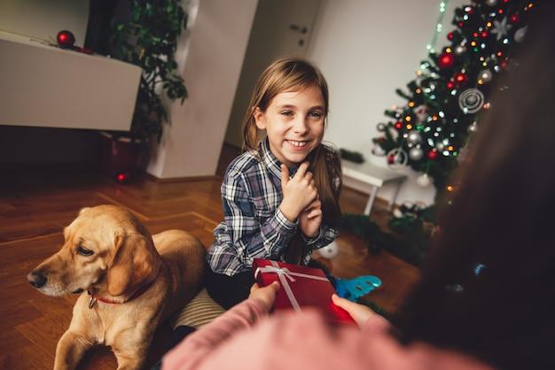 Niña dando un regalo de navidad a su amiga