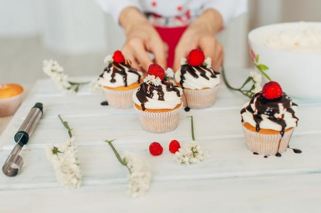 Una niña decora pastelitos con bayas frescas y flores.
