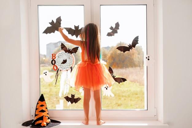 La niña decora la ventana de la habitación con murciélagos y fantasmas de halloween de pie en el alféizar de la ventana.