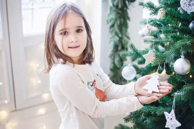 Niña con decoración para árbol de navidad, interior de navidad, preparación para navidad y año nuevo, decoración del hogar