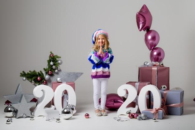 Niña en decoración navideña en luz, cajas de regalo, números grandes 2020, año nuevo y navidad