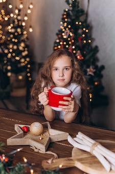 Niña en decoración navideña con té en casa acogedora con coloridas luces de año nuevo