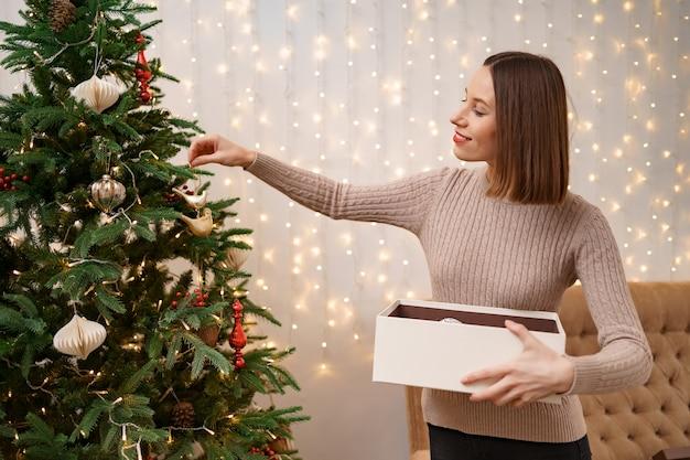 Niña decorando el árbol de navidad, sosteniendo algunos adornos navideños en su mano con luces