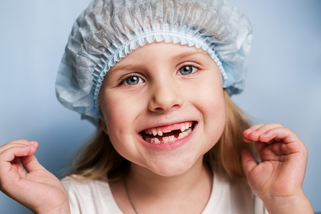 Una niña en el dentista muestra una boca desdentada.