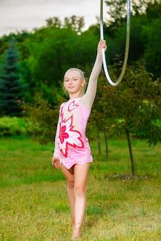 Niña deportiva haciendo ejercicio con hula hoop sobre fondo de parque