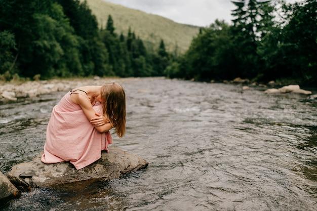 Niña en depresión sentado en piedra en el río