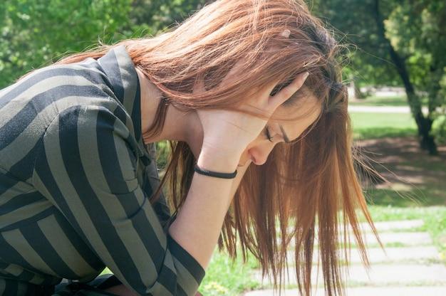 Niña deprimida sentado en el banco en el parque