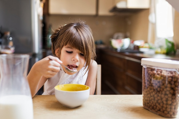 Niña desayunando por la mañana