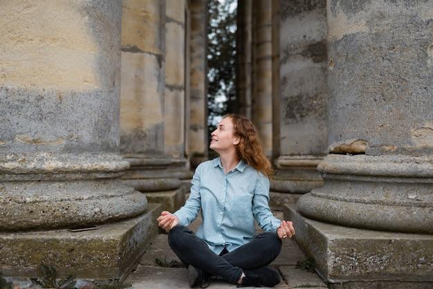 Una niña descansando y meditando entre pilares antiguos. arquitectura y lugar histórico