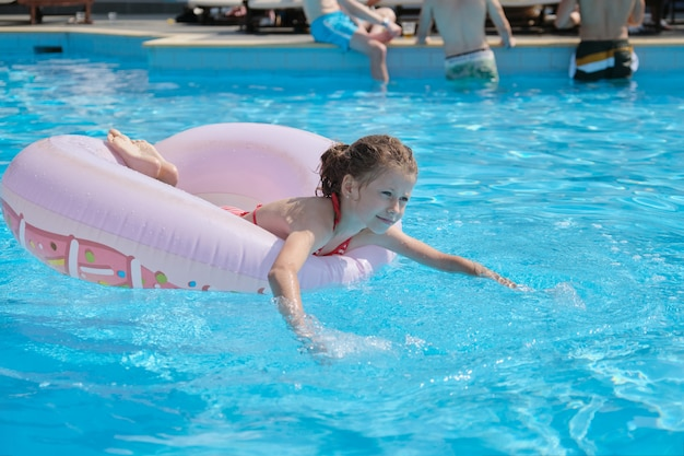 Niña descansando sobre el anillo de natación en la piscina al aire libre