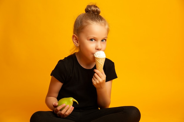 Niña desconcertada en leotardo y zapatos de baile eligiendo entre alimentos saludables y no saludables mientras está sentado con las piernas cruzadas sobre fondo amarillo