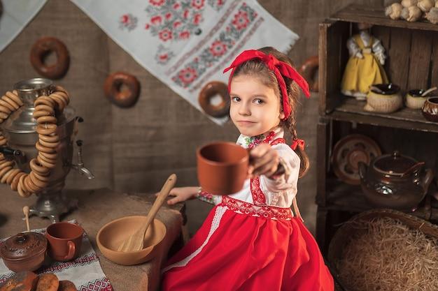 Niña con diadema roja y camisa ornamental bebiendo té de samovar celebrando maslenitsa