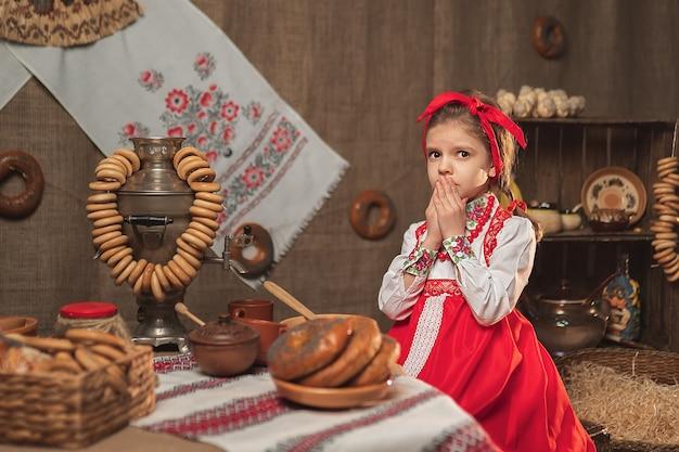 Niña con diadema roja y camisa ornamental sentado en la mesa llena de comida y gran samovar celebrando maslenitsa