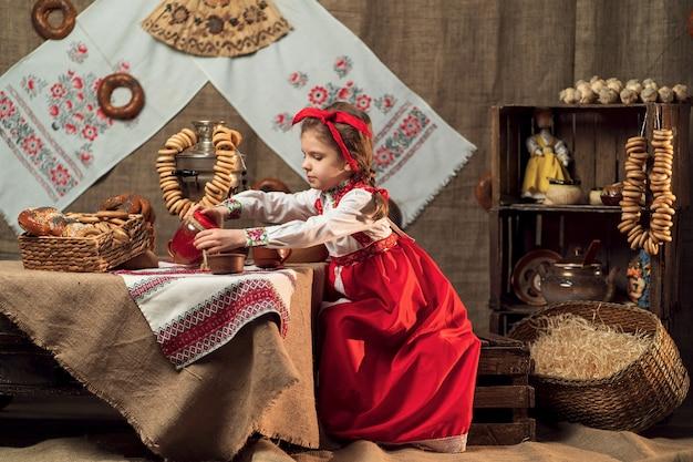 Niña con diadema roja y camisa ornamental vertiendo té de samovar celebrando maslenitsa